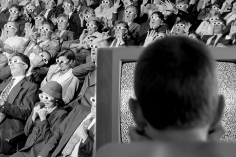 Audience in a movie theater, boy watching TV.
